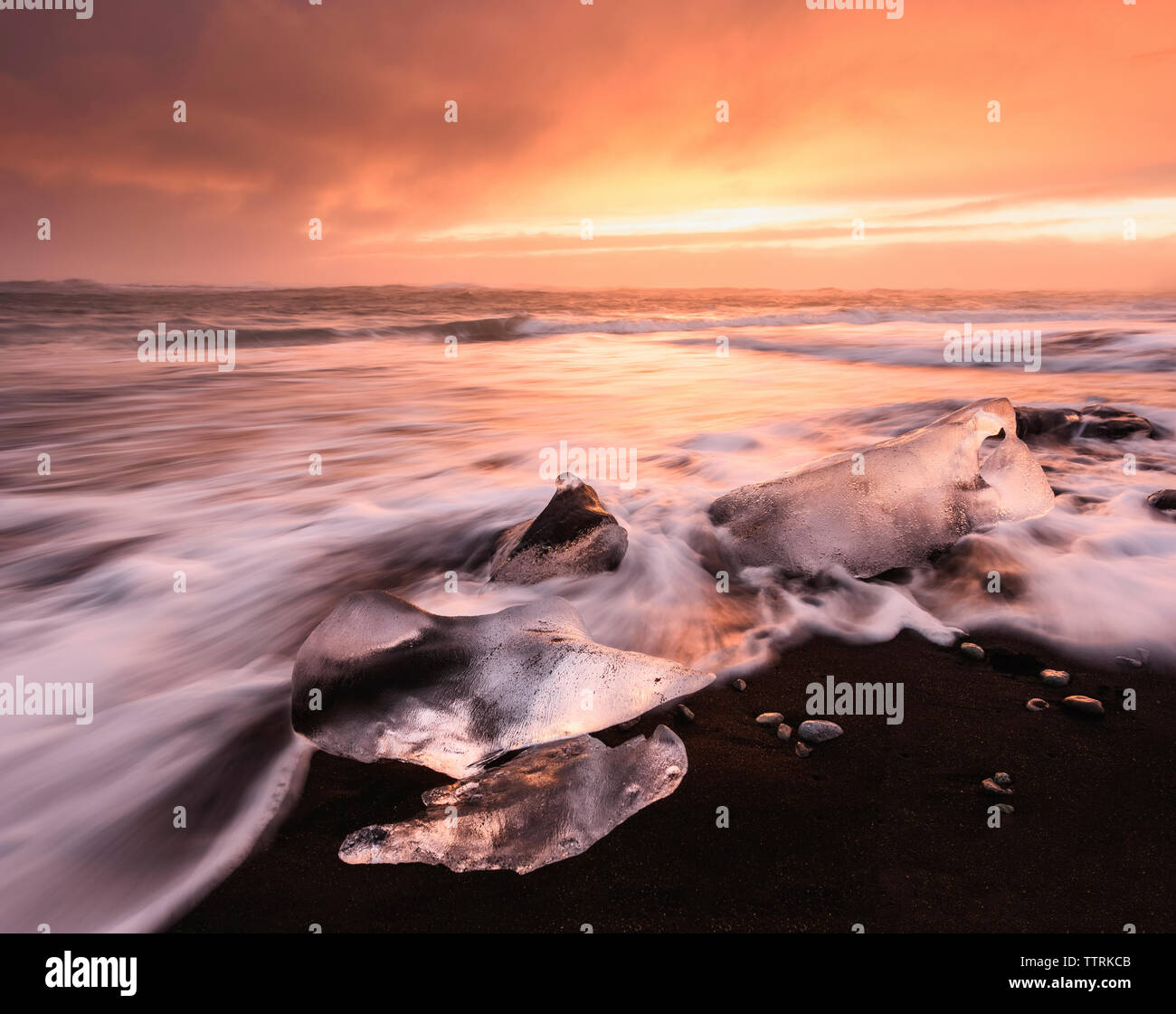 Scenic view of Jokulsarlon Lagoon against cloudy sky during sunset - Stock Image