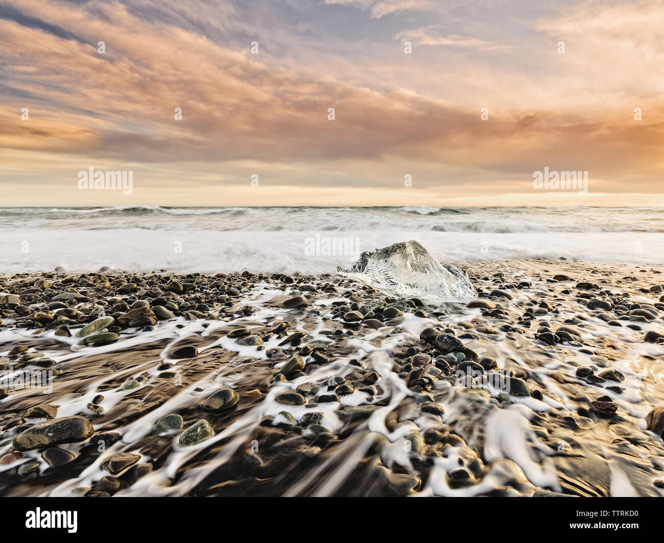 Scenic view of Jokulsarlon Lagoon against cloudy sky during sunset Stock Photo