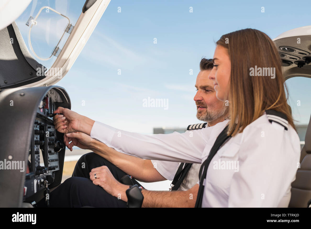 Side view of male pilot teaching female trainee to operate control panel in airplane against blue sky at airport - Stock Image