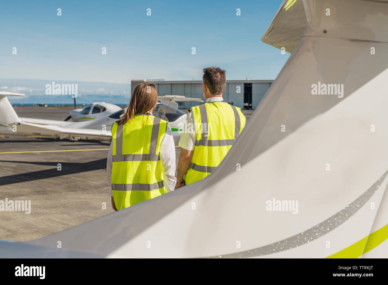 Rear view of engineers wearing reflective clothing standing against blue sky at airport runway - Stock Image