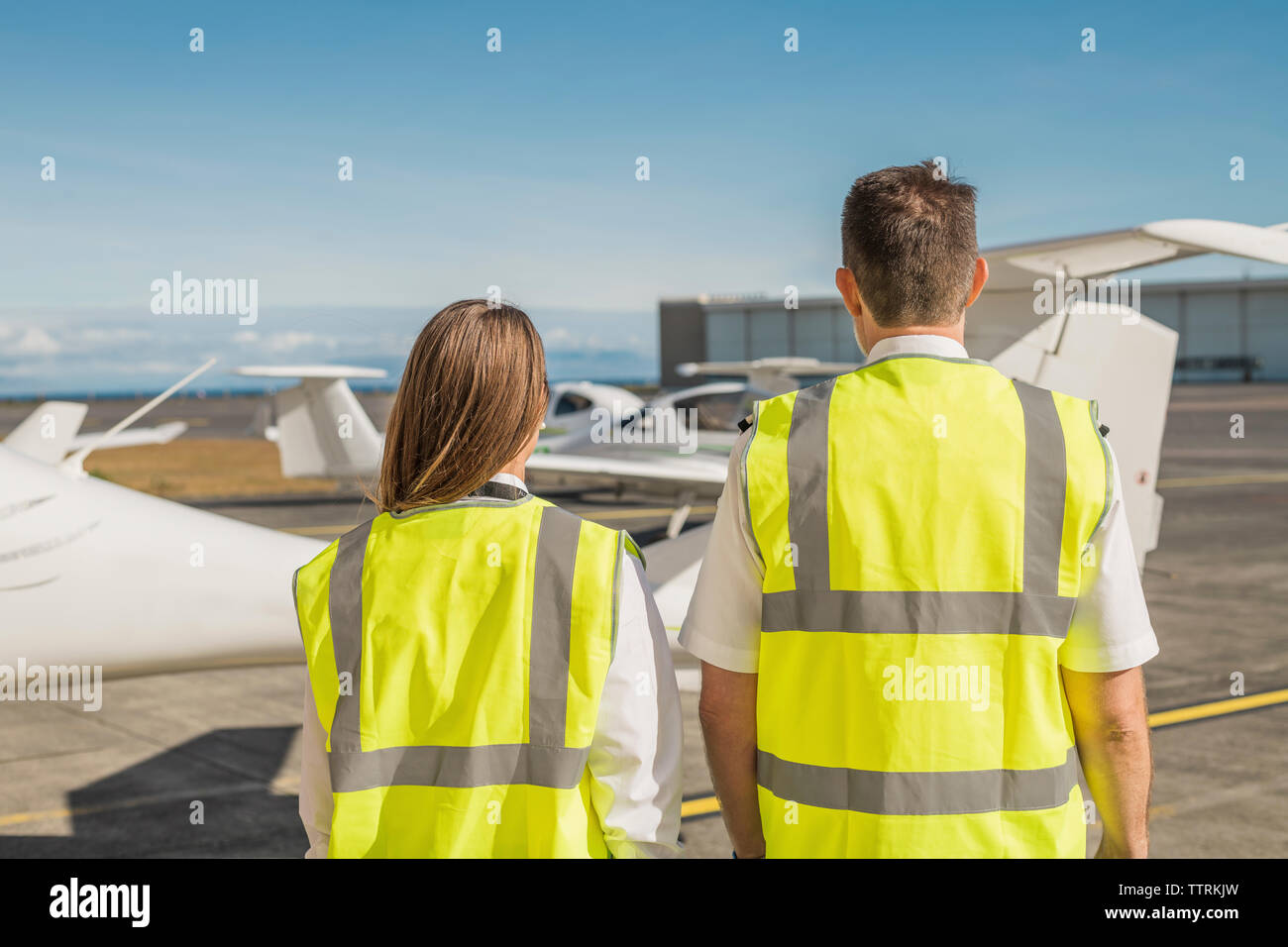 Rear view of engineers in reflective clothing standing against blue sky at airport runway - Stock Image