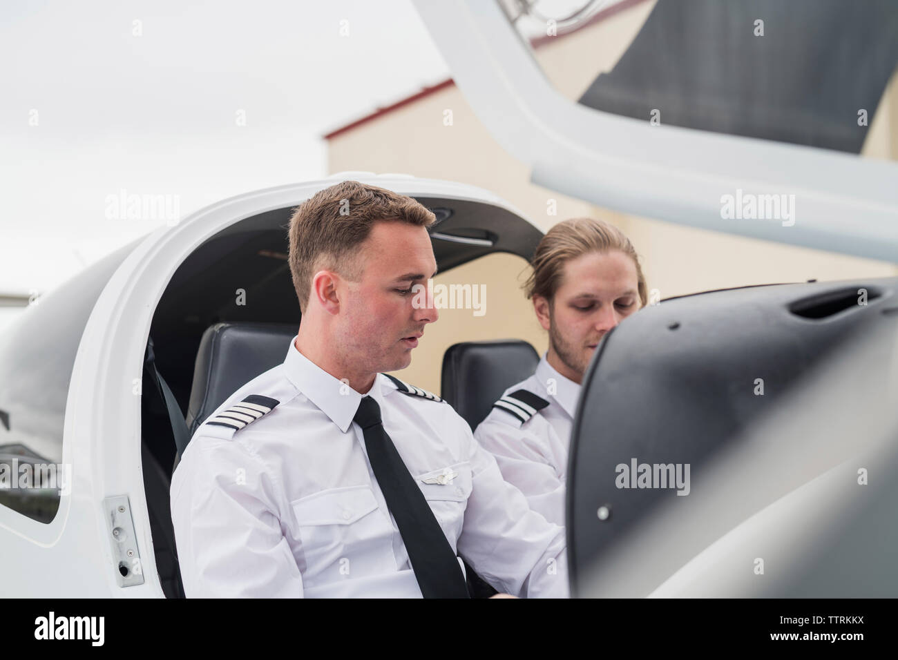 Male pilot guiding trainee while sitting in airplane against sky at airport - Stock Image