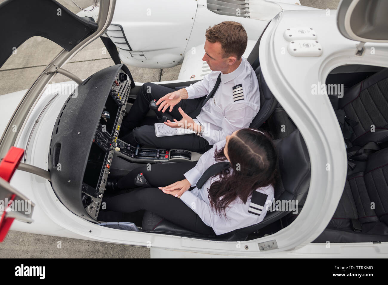 High angle view of male pilot guiding female trainee while sitting in airplane at airport runway - Stock Image