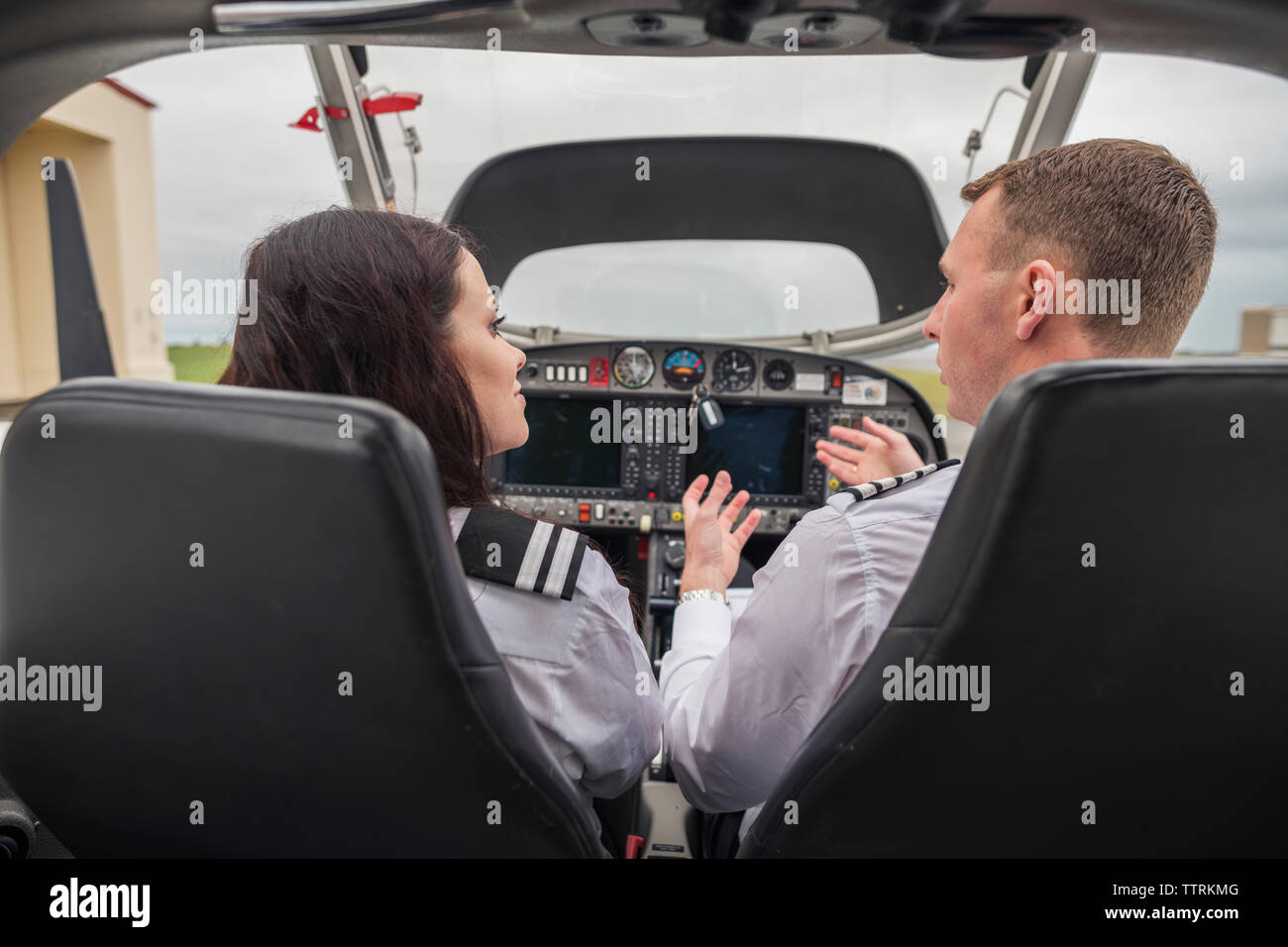 Rear view of male pilot giving training to female trainee while sitting in airplane at airport - Stock Image