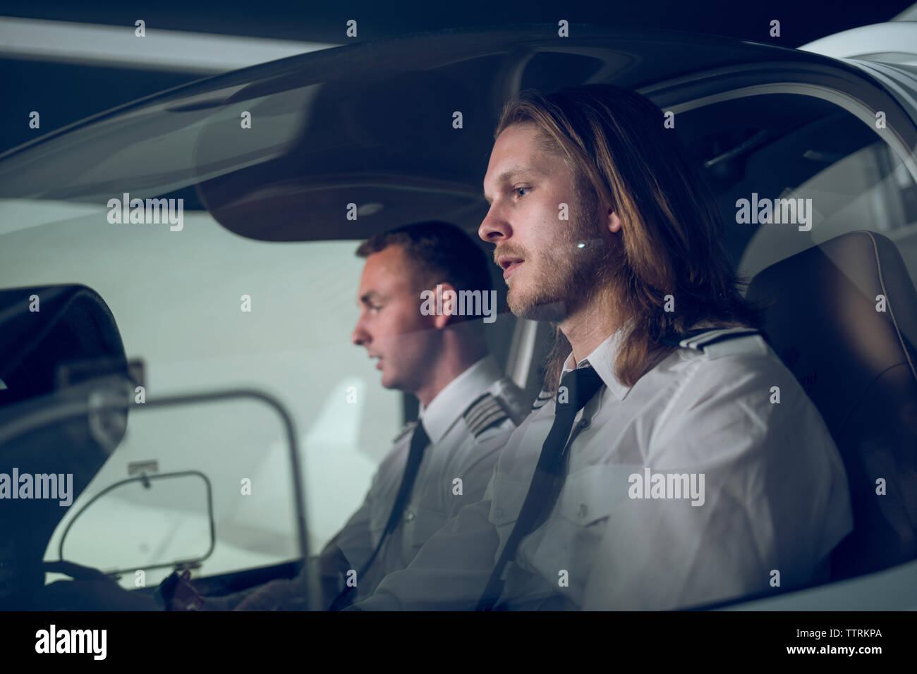 Side view of male pilot with trainee flying in flight simulator - Stock Image
