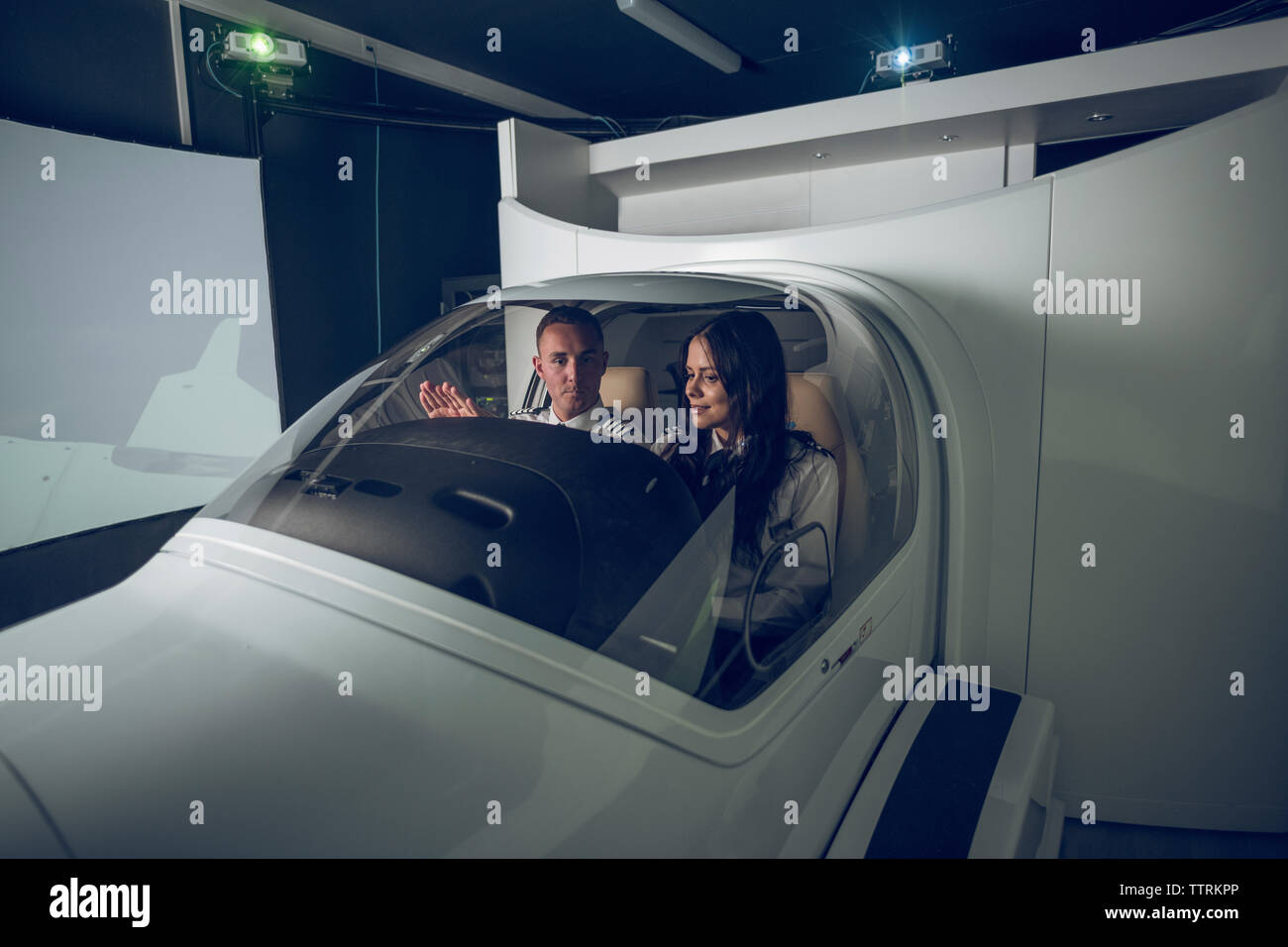 Male pilot guiding female trainee in flight simulator - Stock Image