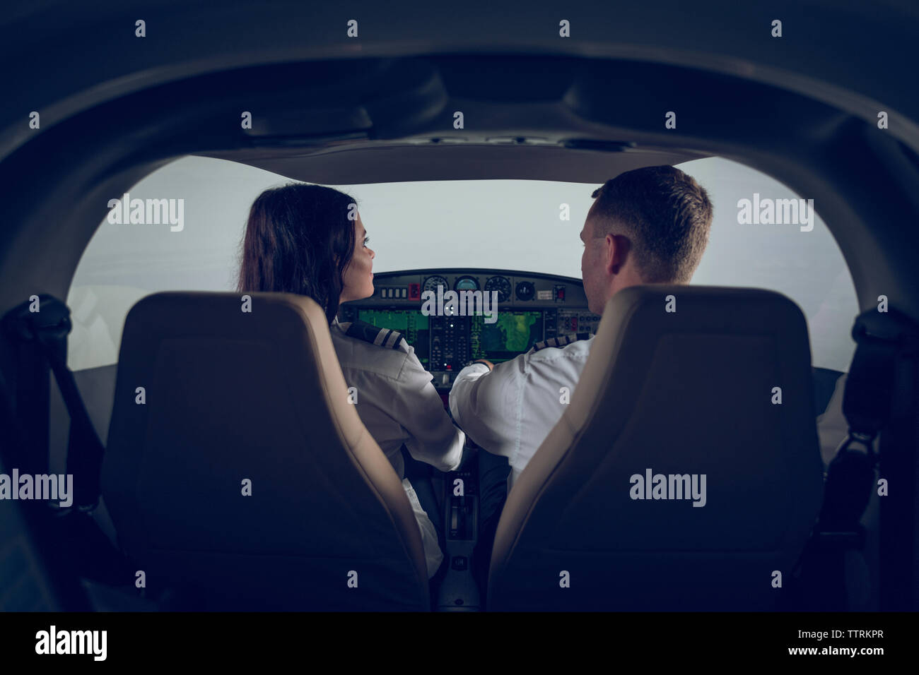 Rear view of male pilot guiding female trainee in flight simulator - Stock Image