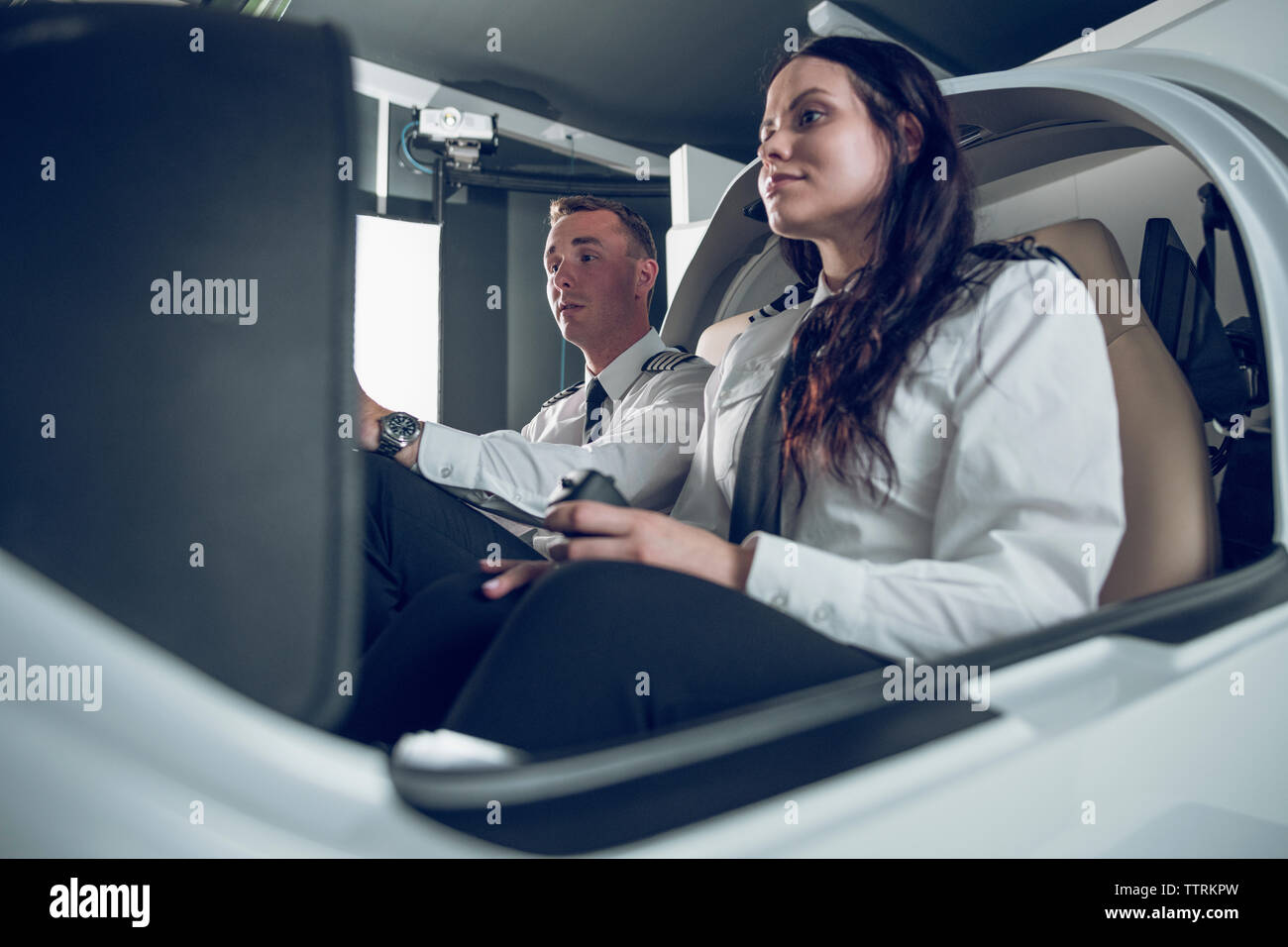 Low angle view of male pilot guiding female trainee in flying flight simulator - Stock Image