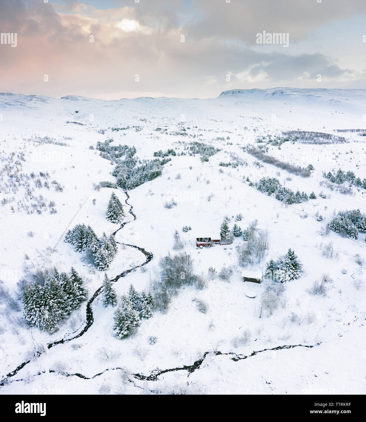 Drone view of picturesque country houses near narrow river between coniferous woods and wild lands in snow in winter - Stock Image