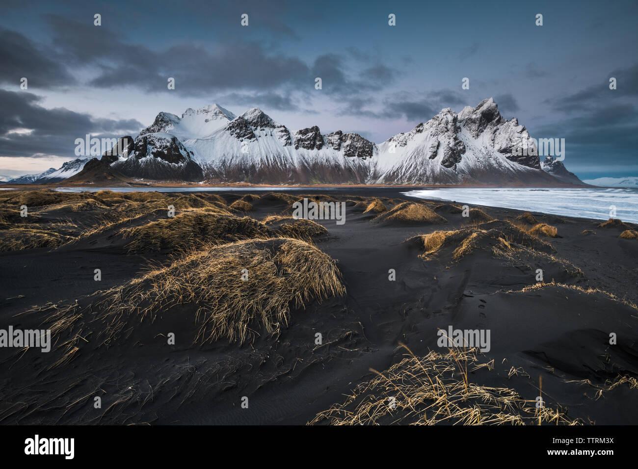 Dark ground of wild lands near river and high rock hills in snow in Vestrahorn, Stokksnes, Iceland Stock Photo