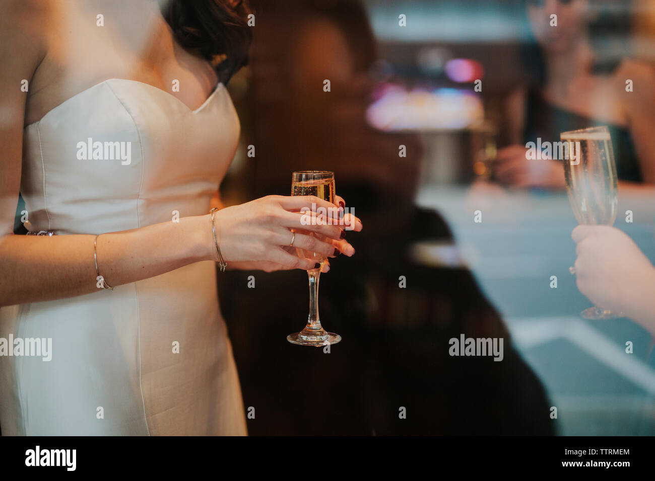 Midsection of bride holding drink seen through window - Stock Image