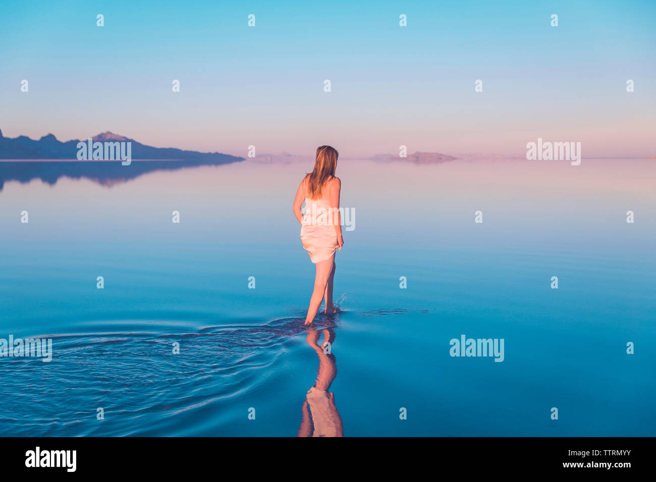 Rear view of woman walking in lake at Bonneville Salt Flats against clear sky Stock Photo