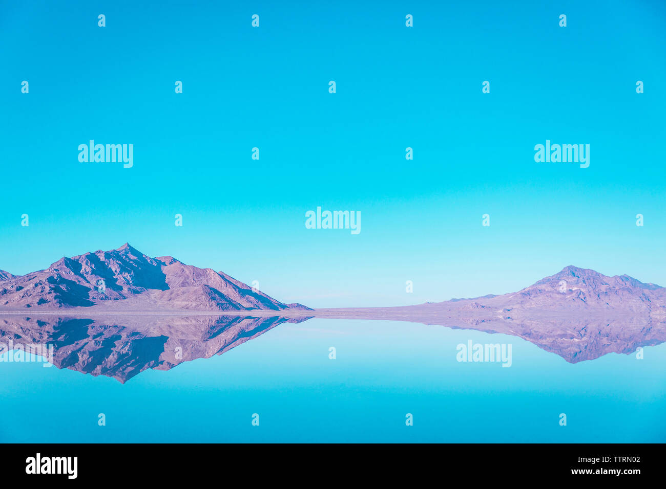 Scenic view of mountains reflecting in lake at Bonneville Salt Flats against blue sky Stock Photo