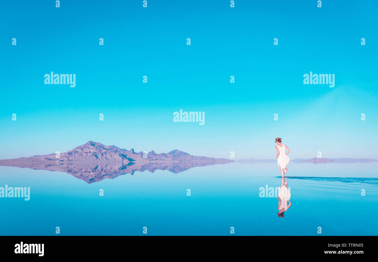 Woman walking in lake by mountain at Bonneville Salt Flats against blue sky Stock Photo