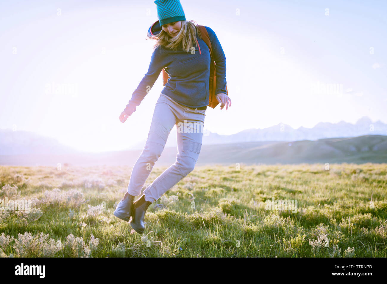 Female hiker jumping on grassy field against sky - Stock Image