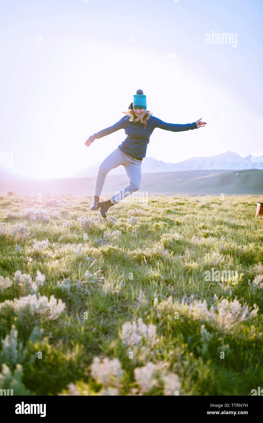 Full length of female hiker jumping on grassy field against sky - Stock Image