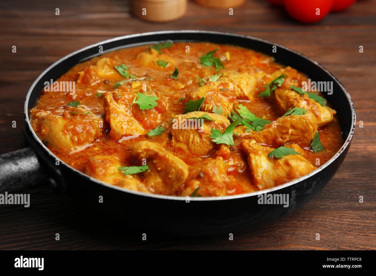Tasty chicken curry in pan on wooden background - Stock Image