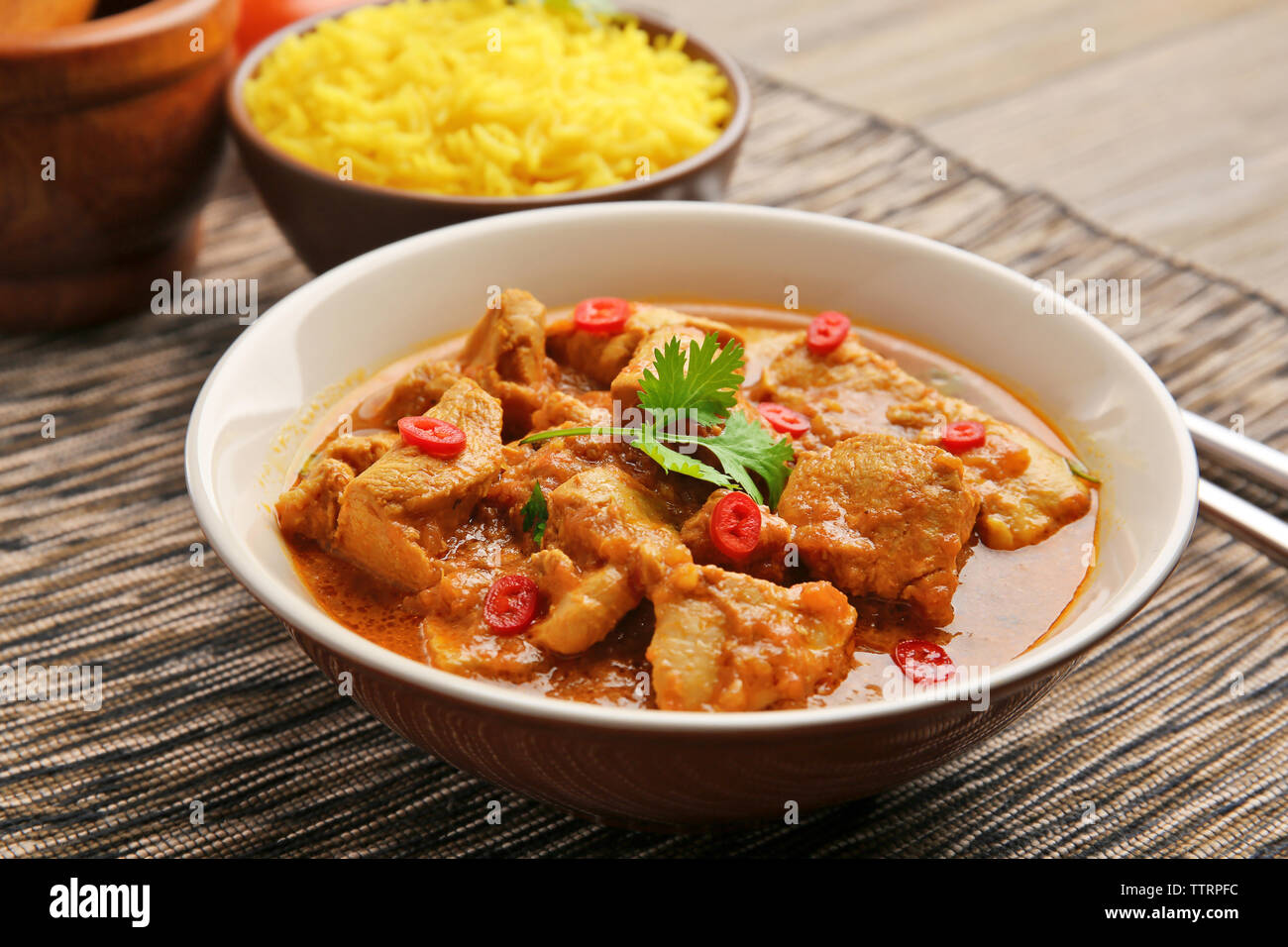 Tasty dinner with chicken curry in plate on table - Stock Image