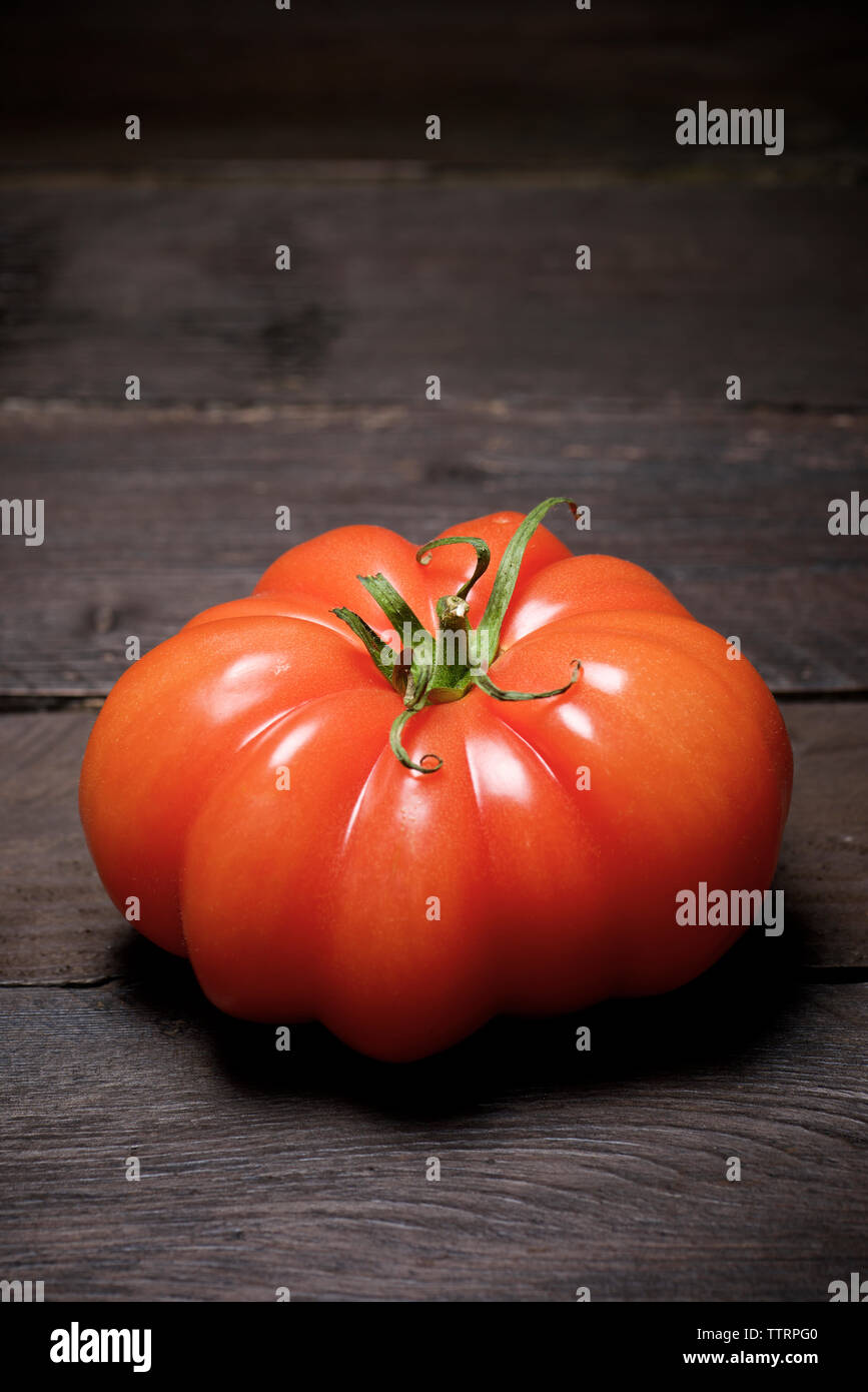 Close-up of tomato on wooden table - Stock Image