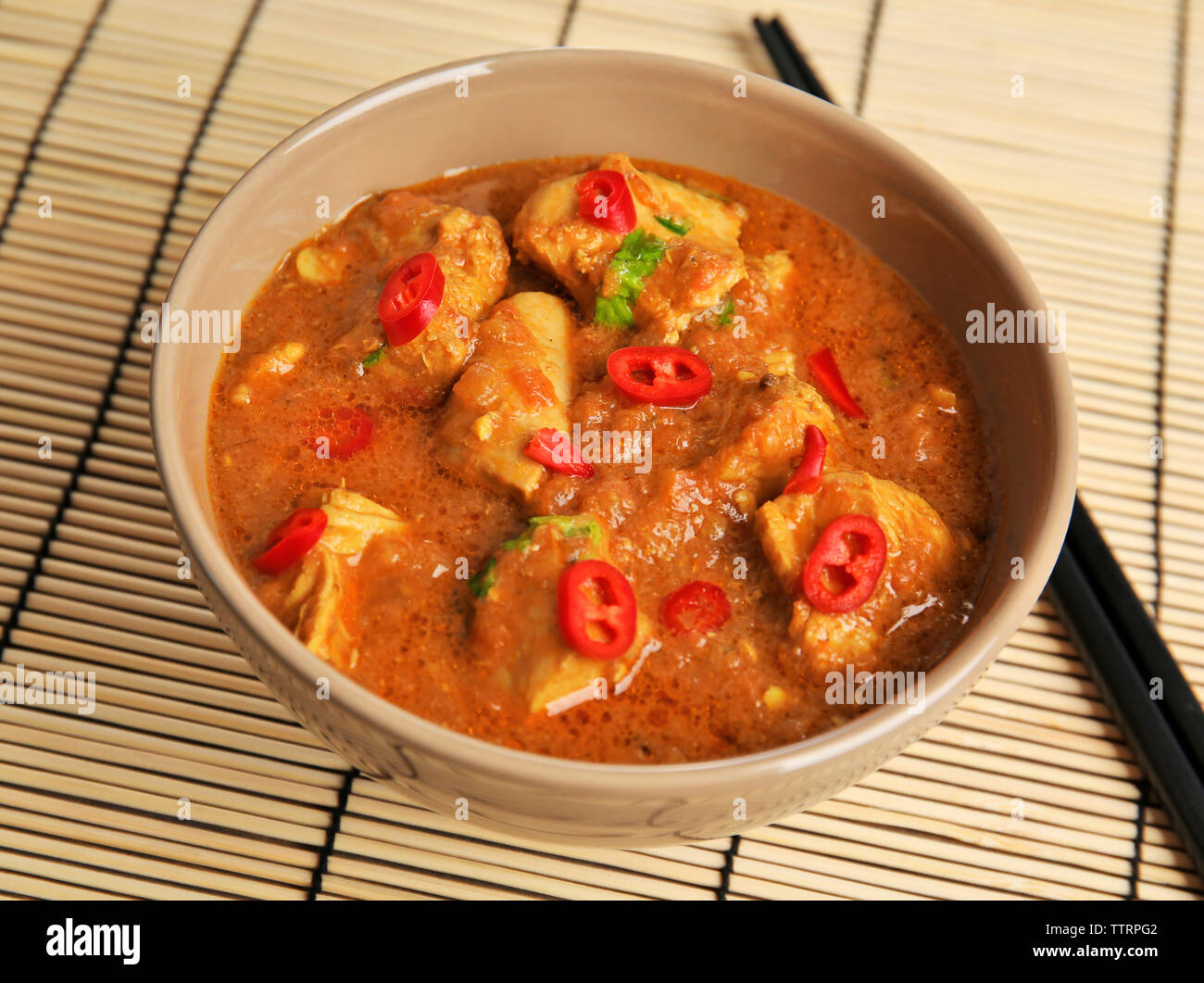 Tasty chicken curry in bowl and chopsticks on bamboo mat - Stock Image