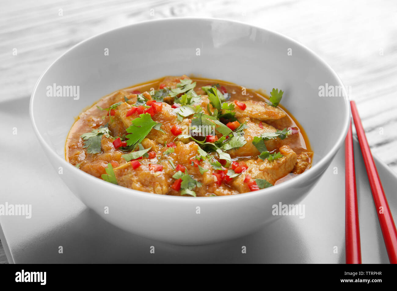 Tasty chicken curry in plate and chopsticks, closeup - Stock Image