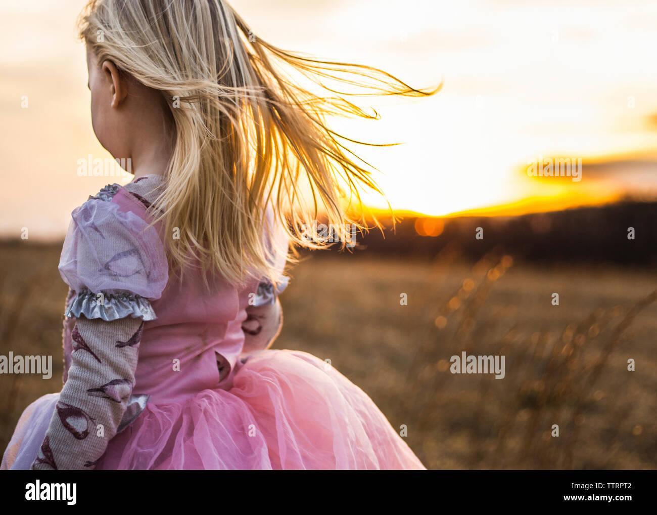 Girl walking on field against sky during sunset - Stock Image