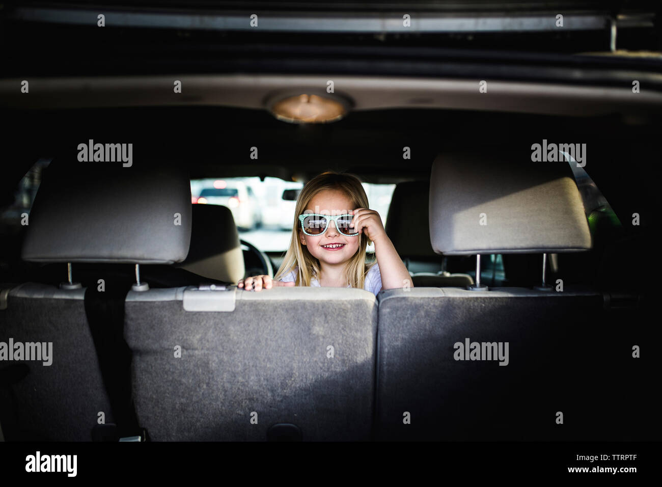 Portrait of girl wearing sunglasses while sitting in car Stock Photo