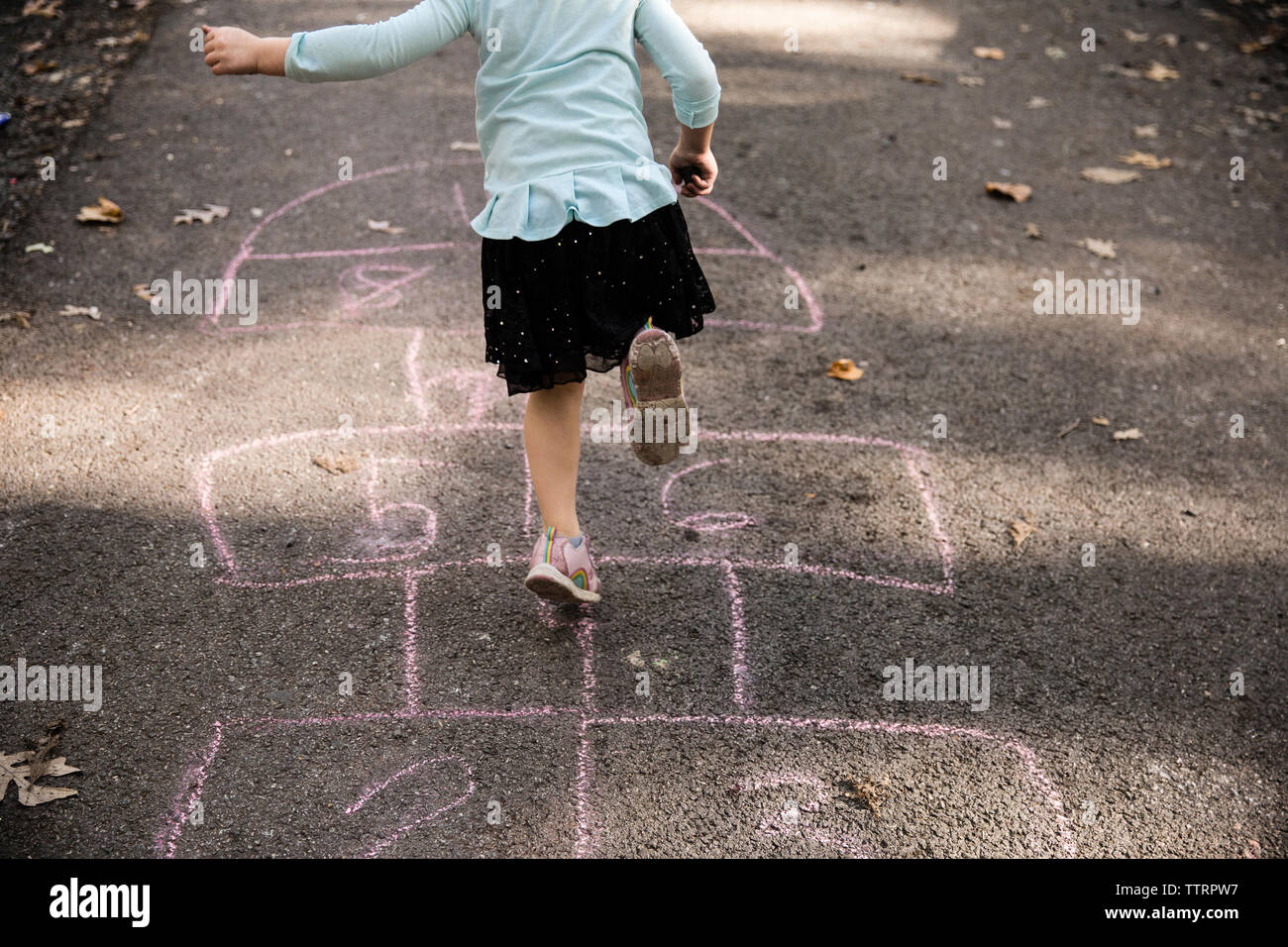 Low section of girl playing on hopscotch - Stock Image
