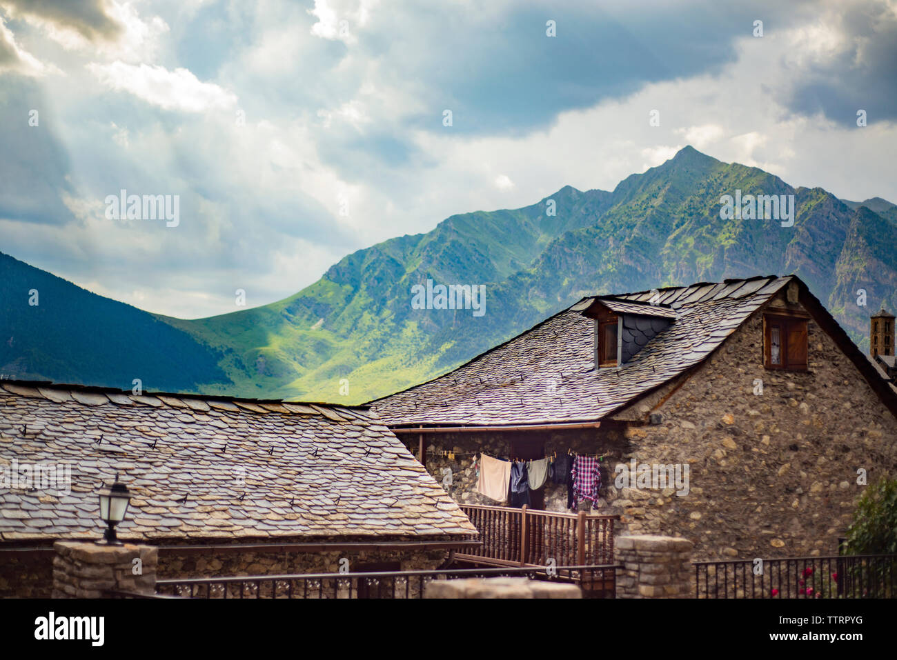 Houses and mountains against cloudy sky - Stock Image