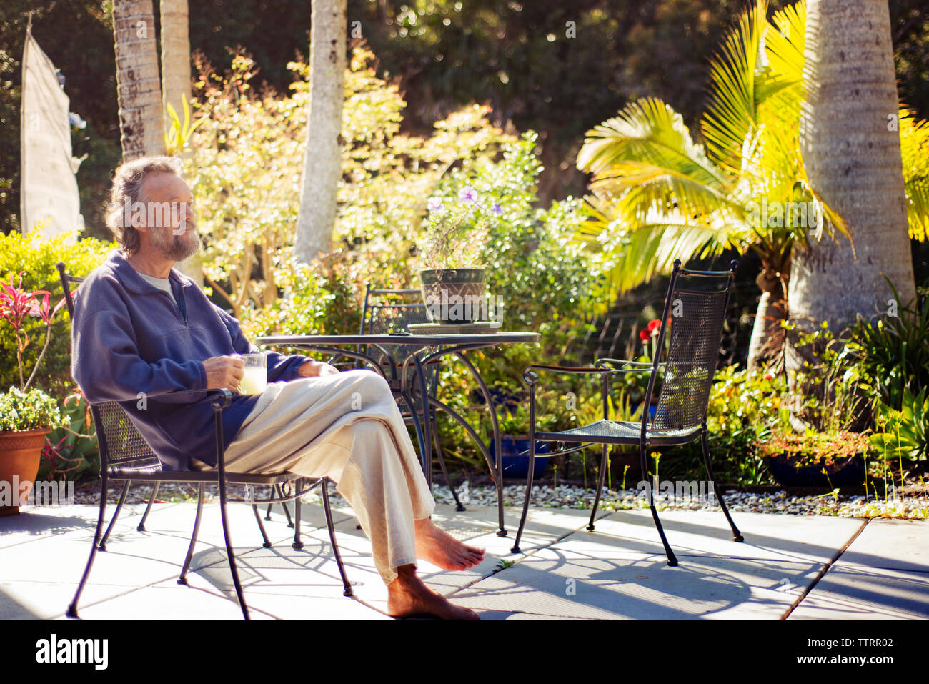 Thoughtful happy senior man sitting on chair in back yard - Stock Image