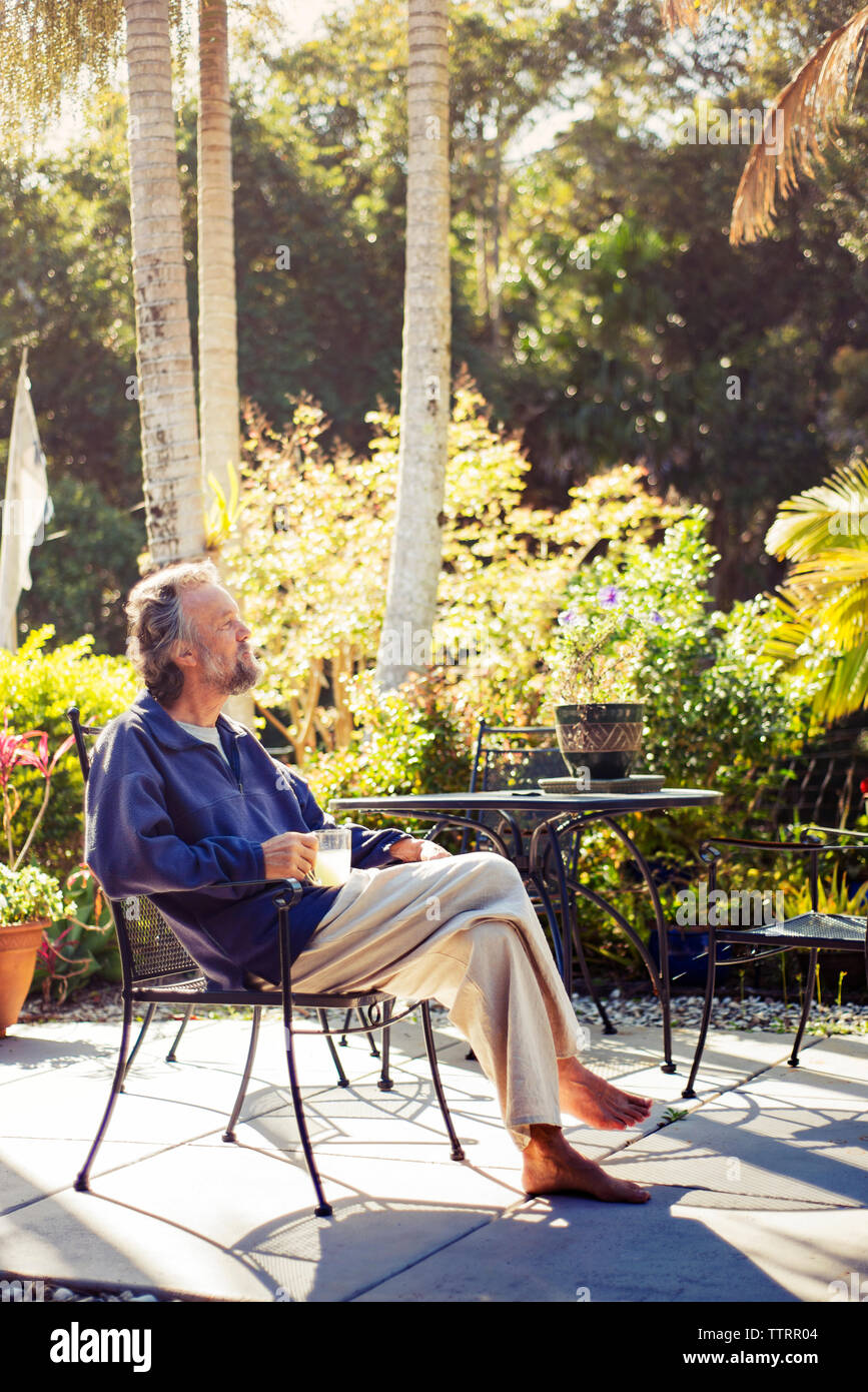 Thoughtful senior man sitting on chair in back yard - Stock Image