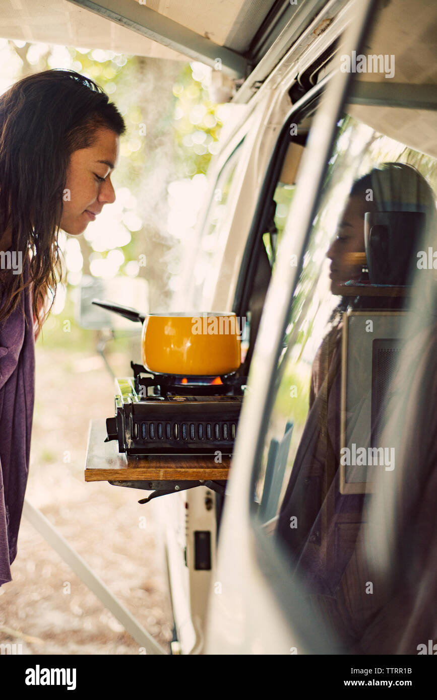 Side view of smiling woman looking at saucepan on stove in travel trailer - Stock Image