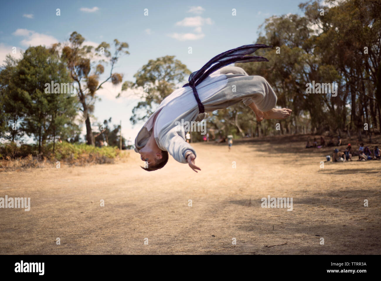 Male martial artist performing back flip on dirt road - Stock Image