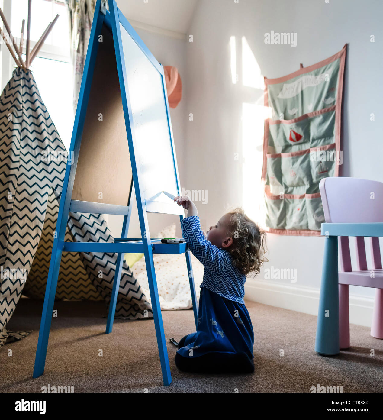 Girl writing on artist's canvas while sitting on rug at home - Stock Image