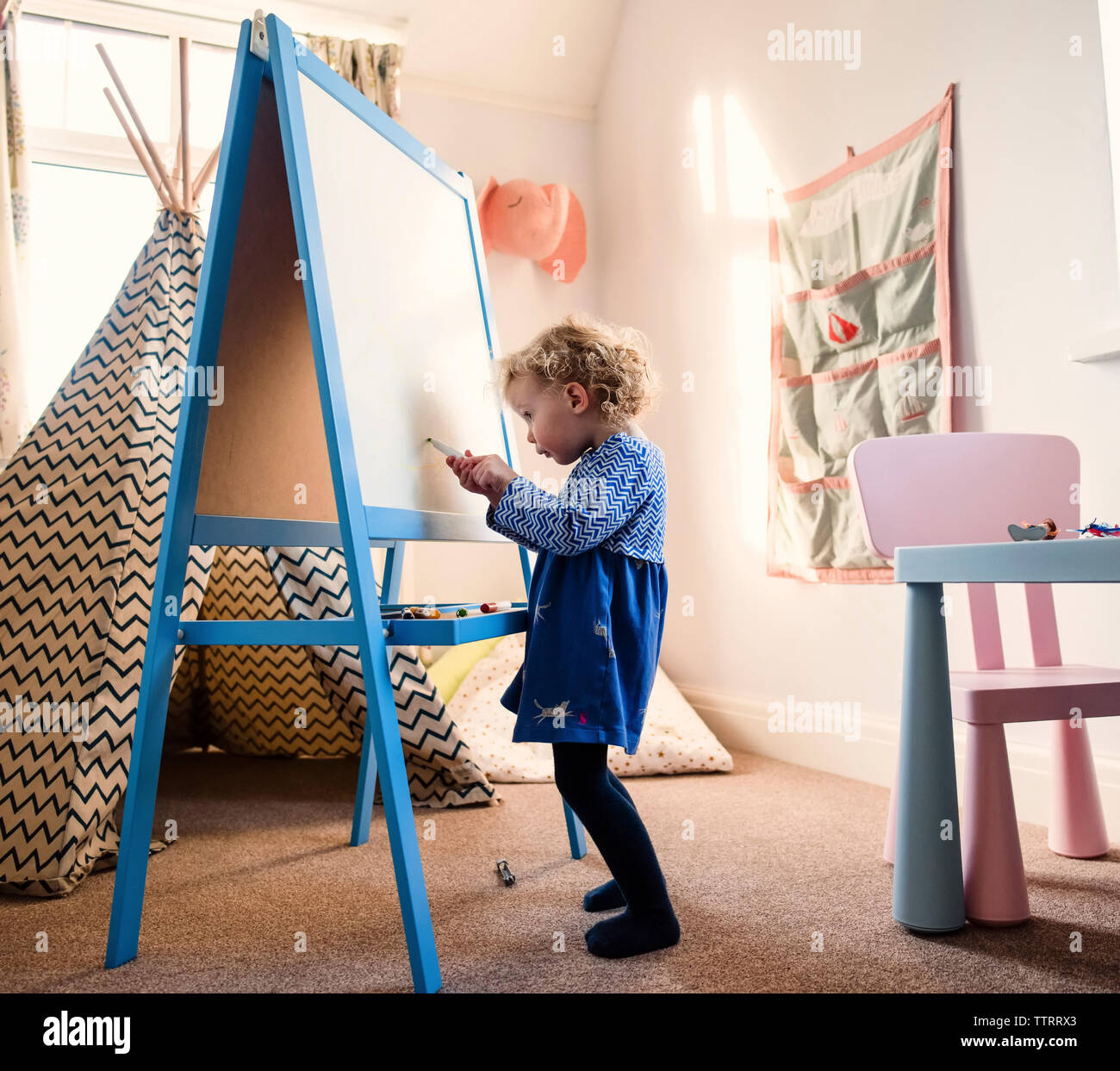 Girl drawing on artist's canvas while standing on rug at home - Stock Image