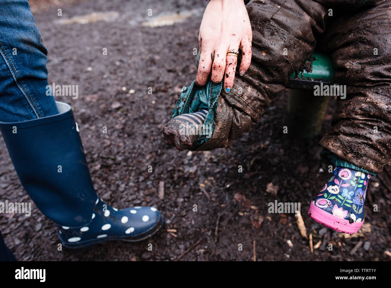 Cropped image of mother holding child's messy pants sitting on slide at park - Stock Image