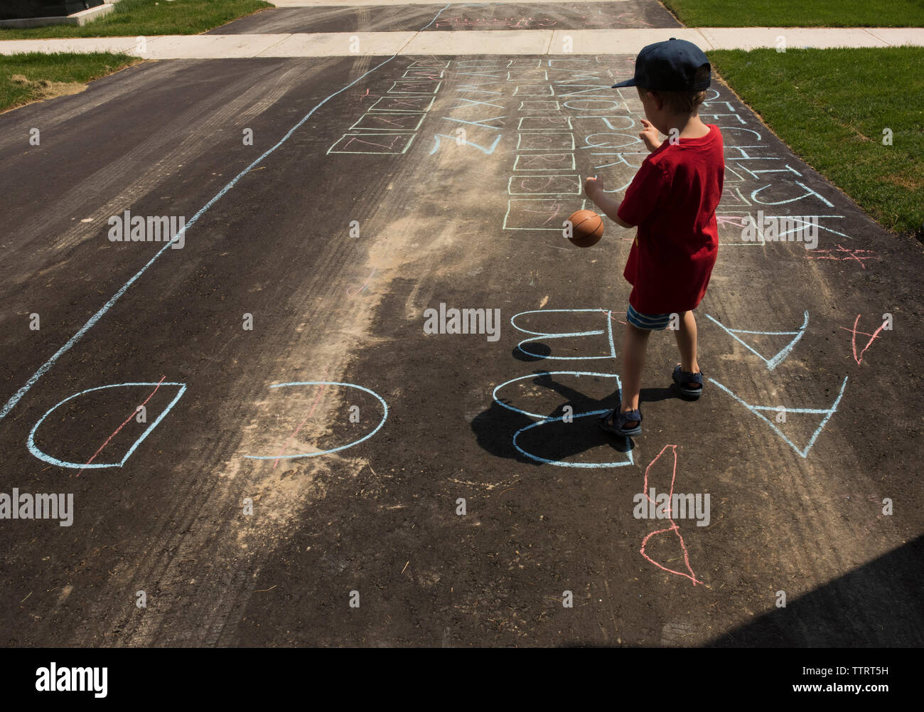 Rear view of boy playing with ball while standing on road with chalk drawing - Stock Image