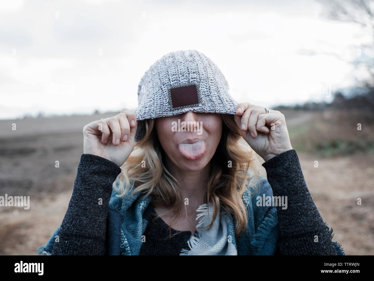 Close-up of playful woman covering eyes with knit hat sticking out tongue while standing on landscape against cloudy sky Stock Photo