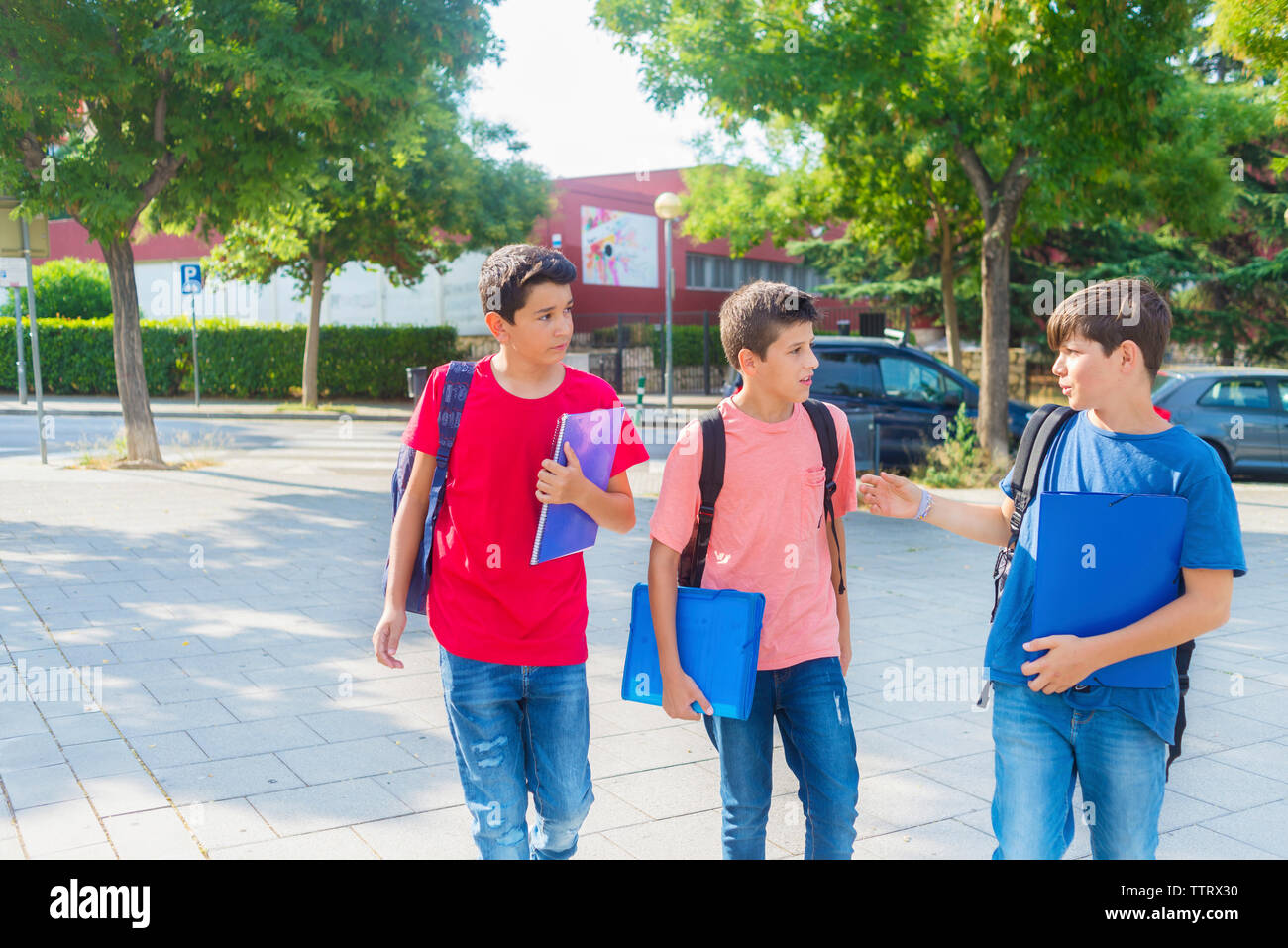 Schoolboys talking while walking on footpath Stock Photo