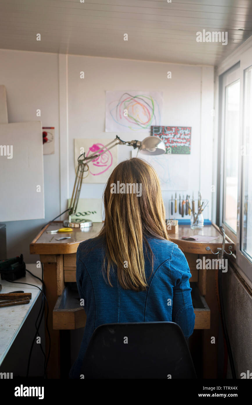 Rear view of female jeweller working in workshop - Stock Image