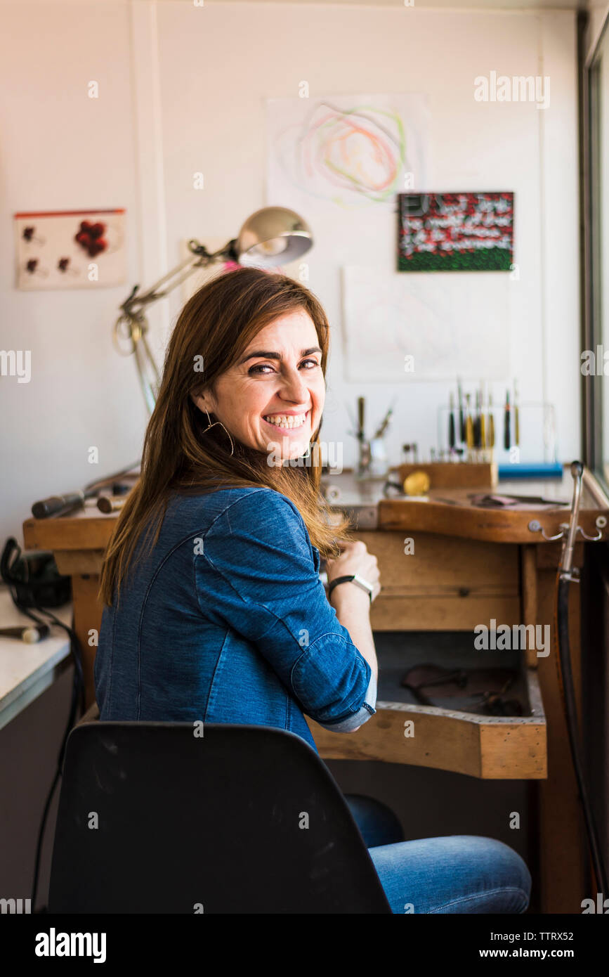 Portrait of happy female jeweller sitting at workbench in workshop - Stock Image