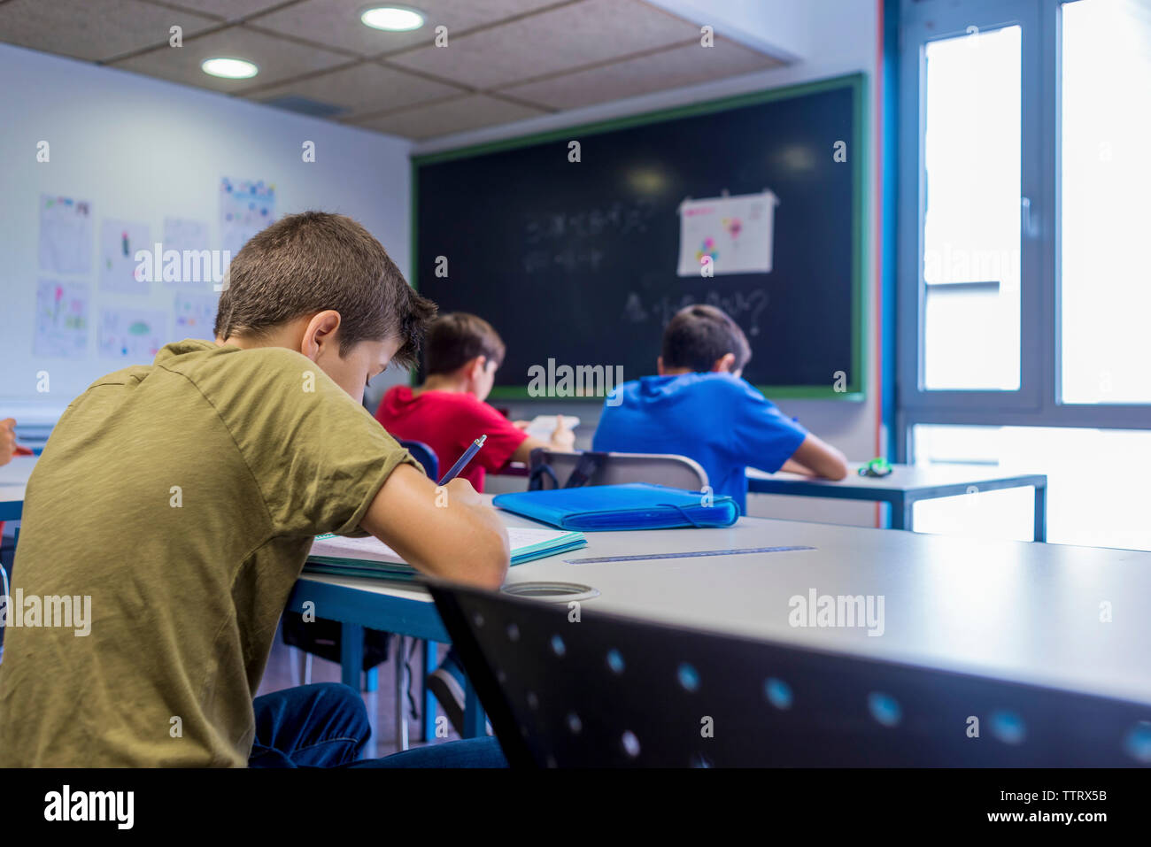 Schoolboys studying while sitting in classroom Stock Photo