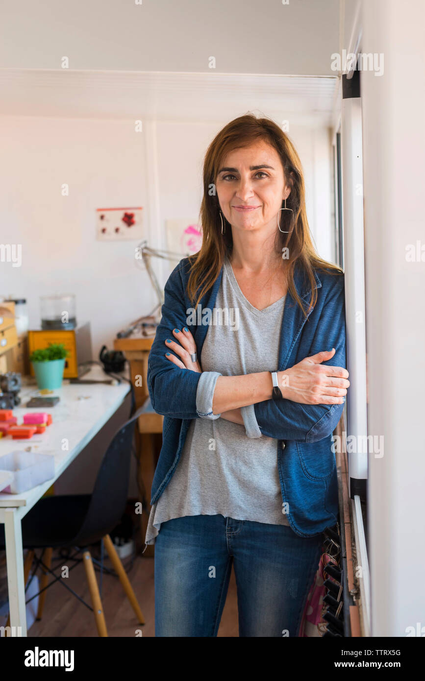 Portrait of female jeweller with arms crossed standing by wall in workshop - Stock Image