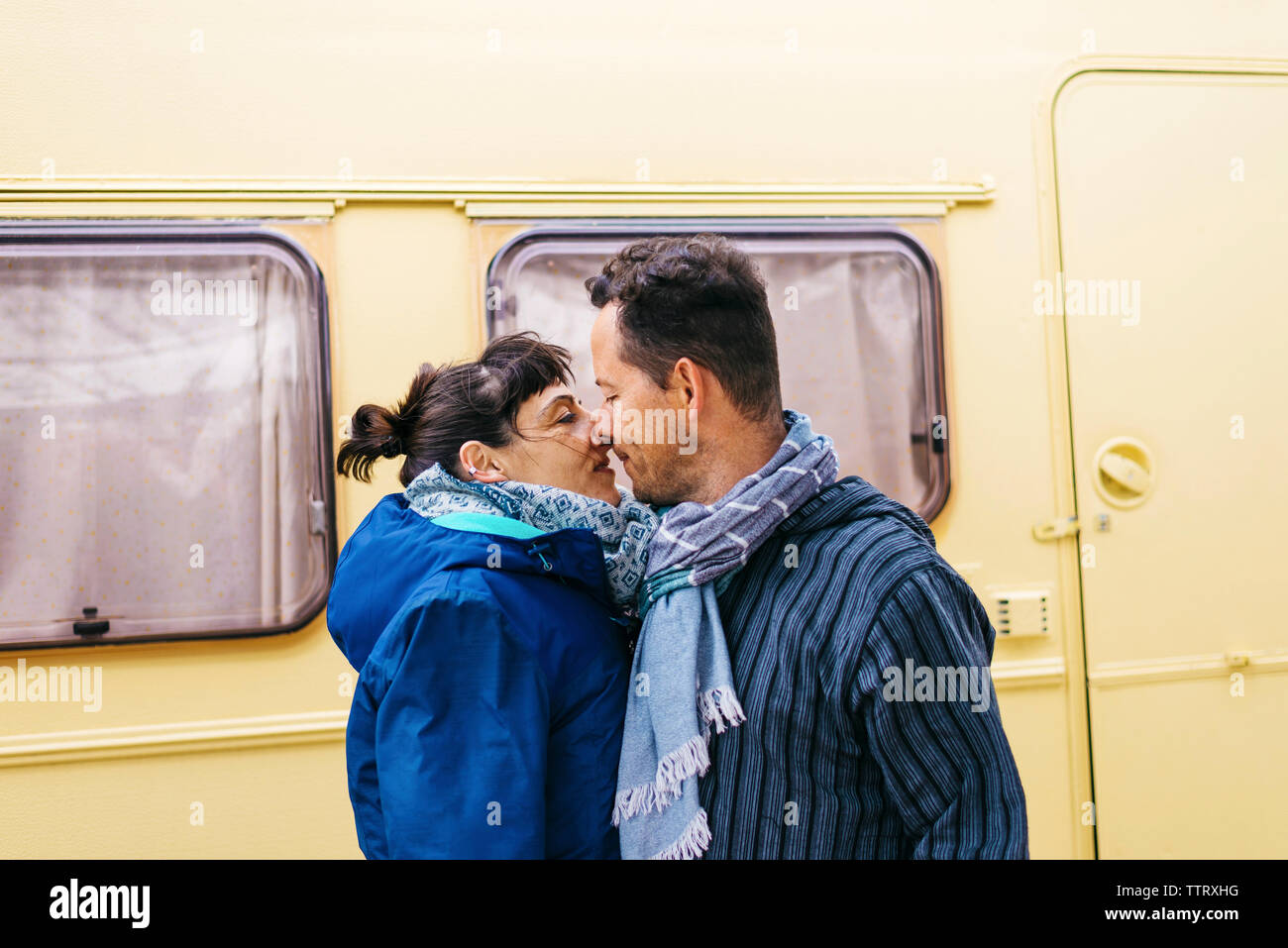 Couple standing while kissing outdoors Stock Photo