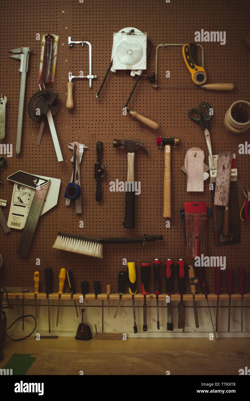 Hand tools hanging on pegboard at guitar workshop - Stock Image