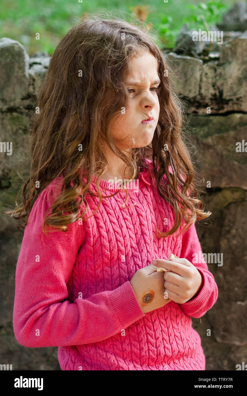 Angry girl scowling while standing against stone wall - Stock Image