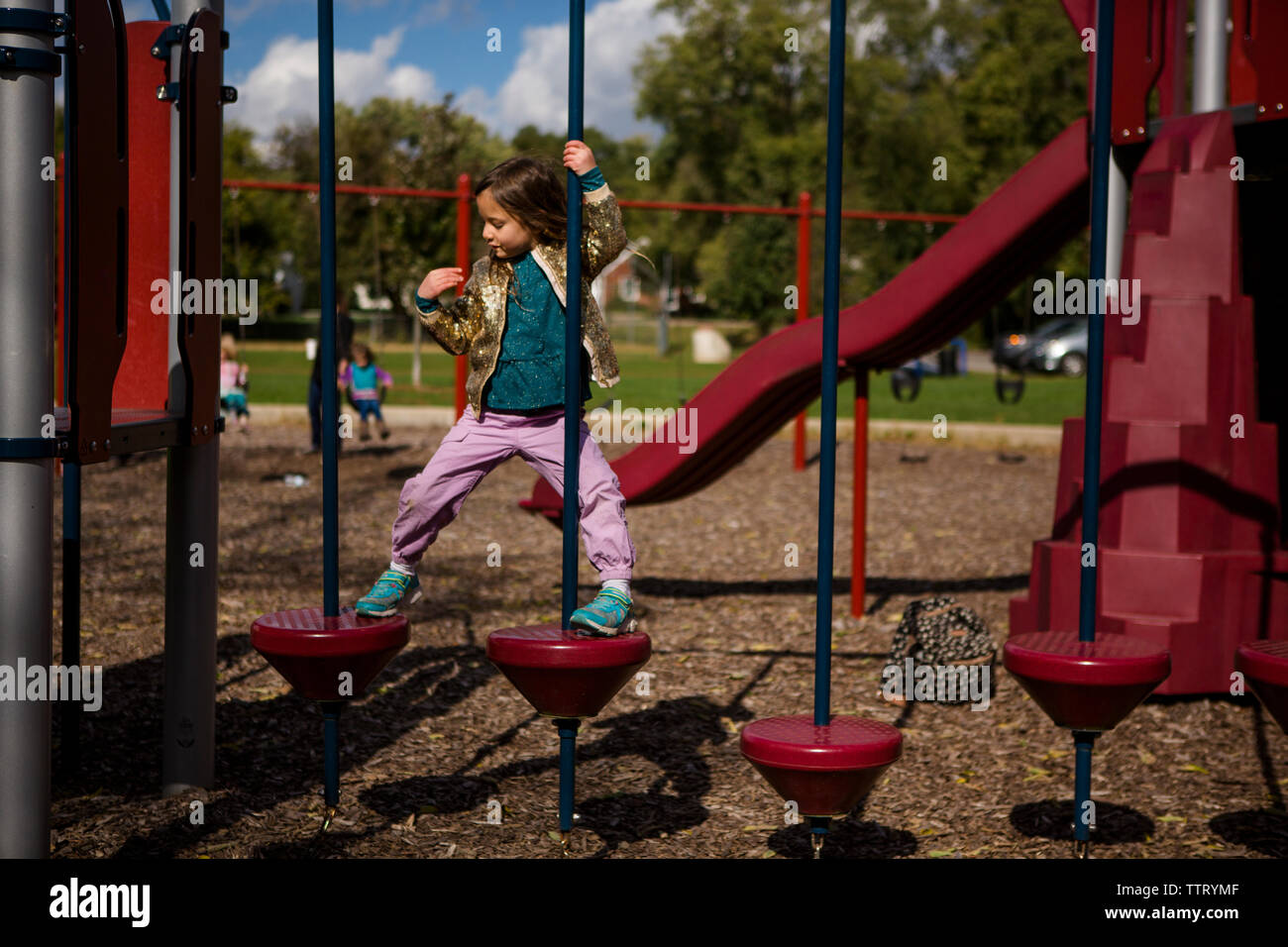 A proud independent little girl climbs on a playground Stock Photo
