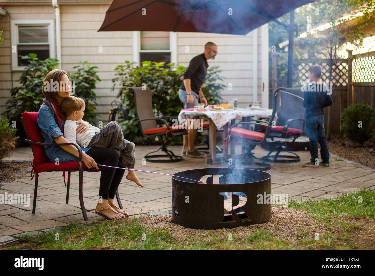 a family sits on their patio preparing dinner together Stock Photo