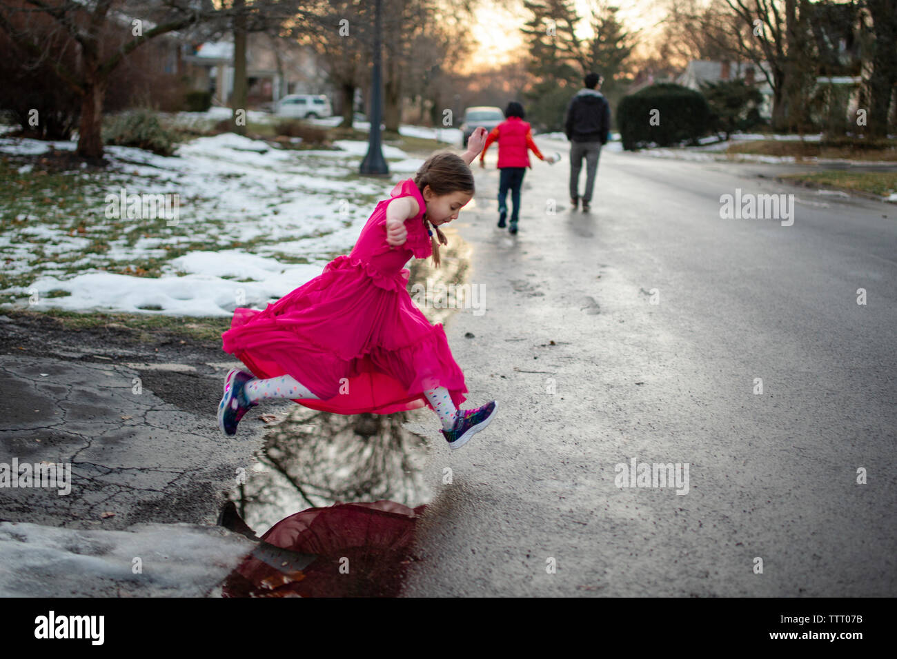 A little girl in long dress leaps across puddle on walk with family Stock Photo