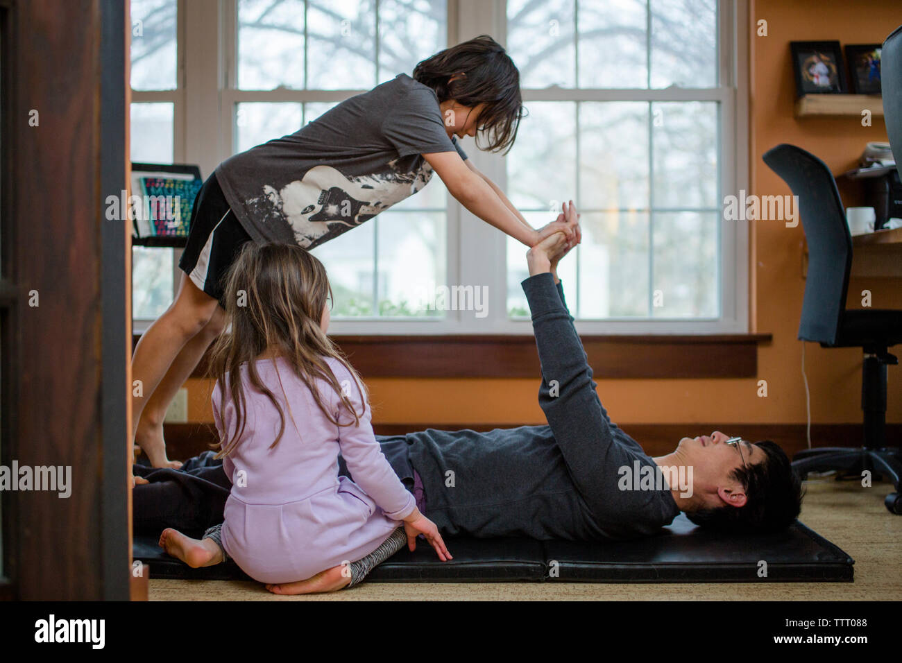 A father does exercise with his two small children inside a home Stock Photo